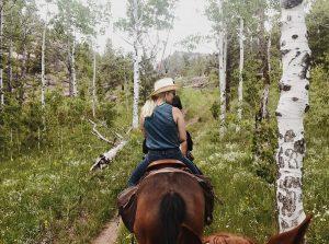 Guests ride between aspen trees