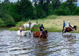 Playing in the pond with horses. Affordable all-inclusive Guest Ranch Family Vacations