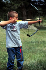 A boy shoots a bow and arrow