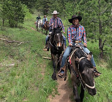Two wranglers smile for a picture while leading a trail ride.